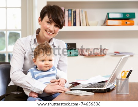 Woman With Baby Working From Home Using Laptop