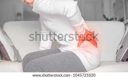 woman with back pain or waist.Acute Inflammation in a woman waist. Female holding hand to spot of back-aches . Concept photo with read spot indicating location of the pain.