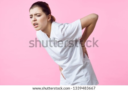 Woman with backache health problem pink background