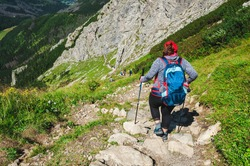 Woman with backpack is walking along the path over the precipice. Extreme hiking trail. Beautiful but dangerous tourist place in mountain. Huge rocks of Small Giewont peak in Tatra Mountains, Poland.
