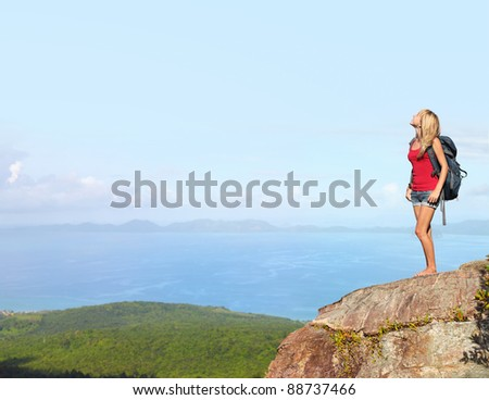 Woman with backpack standing on a top of a mountain and looking to somewhere - stock photo