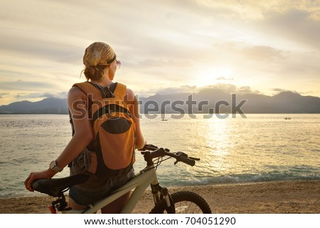 woman with backpack standing on the shore near his bike and enjoying the sunset over the sea on the background of the island
