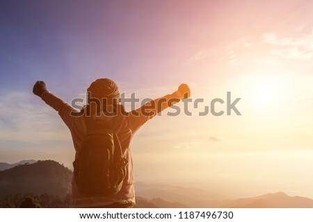 Woman with backpack standing on top of a mountain with raised hands, Successful feeling concept #1187496730