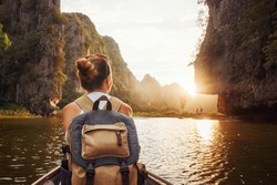 Woman with backpack swims on boat among karst mountains to meet her friends. Tam Coc,  North of Vietnam.