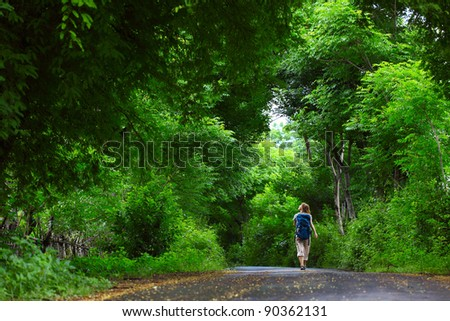 Woman with backpack walking on an asphalt road in a park with green trees