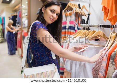 Woman with bag looking through clothes and smiling in shopping mall