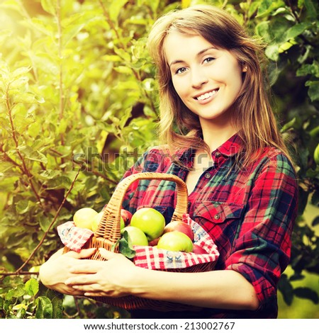Woman with basket of apples in a garden. Young smiling attractive woman is standing with full basket of organic ripe apples in a sunlit orchard. Country happy lifestyle concept. Harvest season.