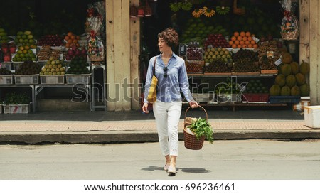 Woman with basket of groceries crossing road