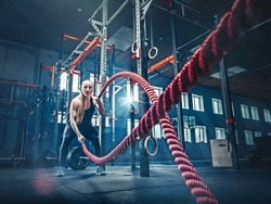 Woman with battle rope battle ropes exercise in the fitness gym. CrossFit concept. gym, sport, rope, training, athlete, workout, exercises concept