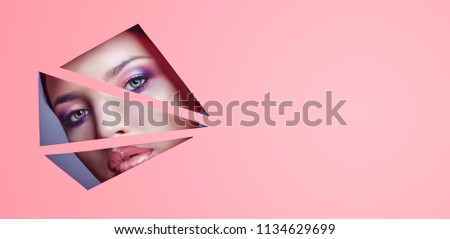 Woman with beautiful bright makeup and pink lipstick looks through triangular slits in pink paper. Advertising cosmetics, professional art makeup, lip gloss, bright color. Girl looks perforated paper
