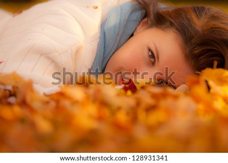 Woman with beautiful eyes laying in autumn leaves