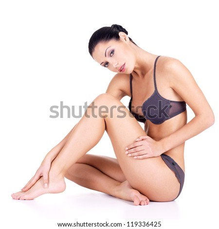 Woman with beautiful legs in bikini sits  on white background