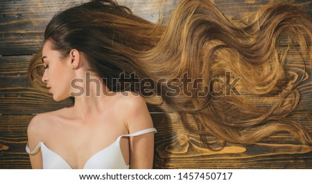 Woman with beautiful long hair on wooden background. Long hair. Closeup woman portrait with very long hair, copy space.Fashion haircut