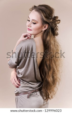 Woman with beautiful long hairstyle very sensuality. Posing in studio
