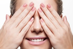 Woman with beautiful natural manicure closes eyes with her hands