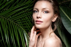 Woman with beautiful skin on a background of tropical exotic leaves in the forest