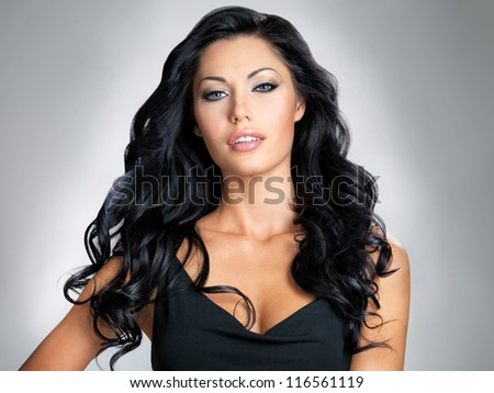 Woman with beauty long brown hair - posing at studio on gray background
