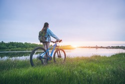 Woman with bicycle on the hill near the river at sunset in spring. Landscape with sporty girl with backpack riding a mountain bike, dirt road, green grass, water in summer. Sport and travel. Cycle
