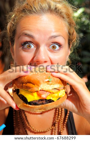 Woman with big round eyes eating a yummy cheeseburger