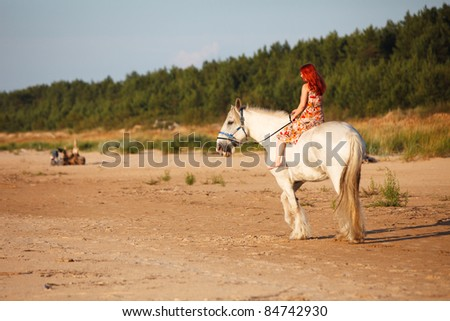 Woman with big white horse riding in beach