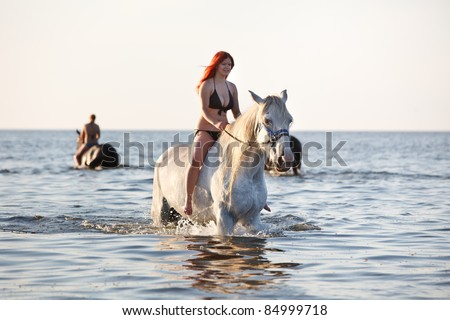 Woman with big white horse swimming in the sea
