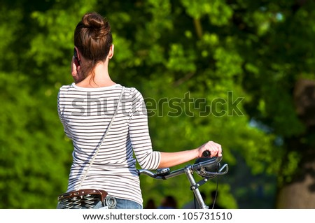 Woman with bike talking on mobile phone in park