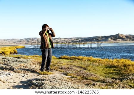 woman with binoculars scanning the horizon