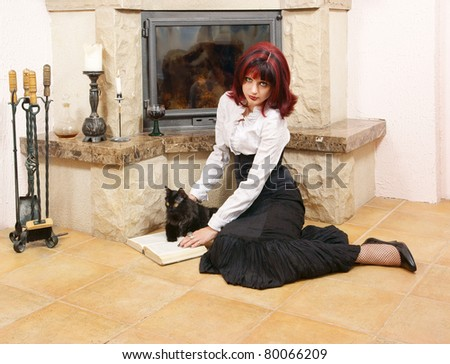 Woman with black cat reading book