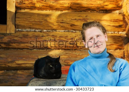 Woman with black cat sitting near her country house