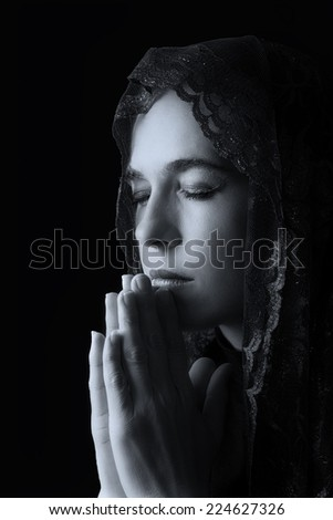 Woman with black head scarf over her head pray for peace