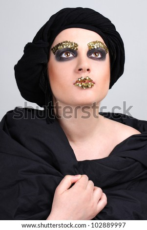 Woman with black make-up and scarf on head