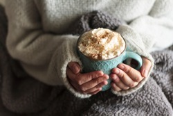 Woman with blanket warming her hands in mug of hot drink with whipped cream