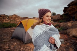 Woman with blanket wrapped around wearing winter cap looking away during camping