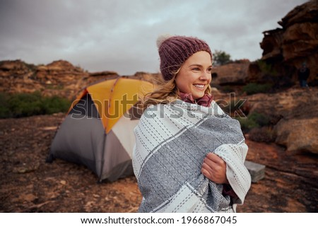 Woman with blanket wrapped around wearing winter cap looking away during camping Stock photo ©