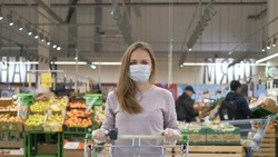 Woman with blond hair wearing a medical mask and rubber gloves stands with a grocery cart in a supermarket against the background of shelves with goods and customers. Protection from the coronavirus