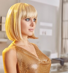 woman with blonde bob haicut and gold tank top in a interior