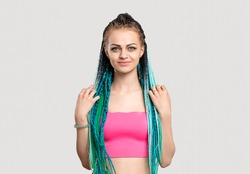 Woman with blue braids. Colorful hair. Portrait of cheerful lady in pink top with ethnic hairstyle isolated on white copy space. Bright dreads. Professional hairdo. Beauty salon.