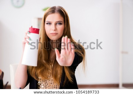Woman with bottle of cream in make-up concept