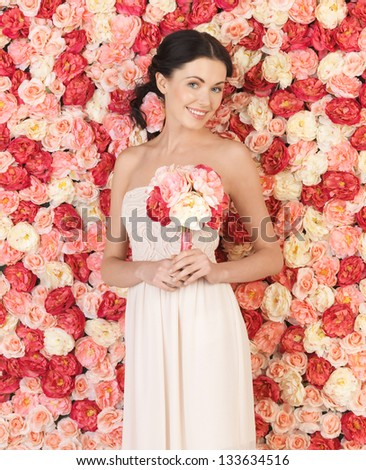 woman with bouquet of flowers and background full of roses