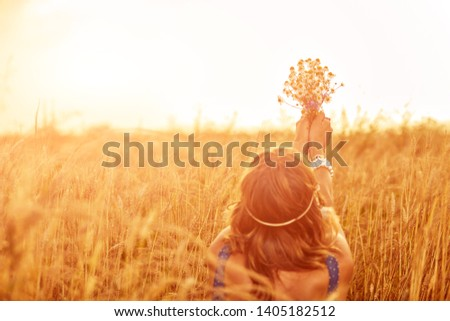 Woman with bouquet of flowers in a wheat field. #1405182512