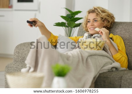 woman with bowl of potato chips watching tv on sofa Сток-фото ©