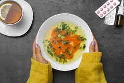 Woman with bowl of soup at grey table, top view. Flu treatment