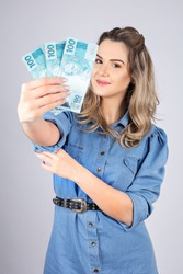 woman with Brazilian real money to give away one hundred reais