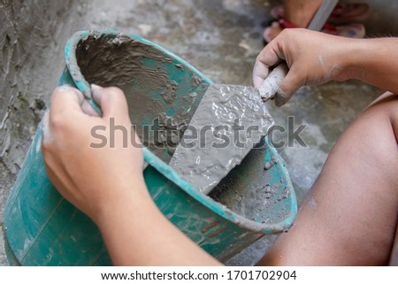 woman with bucket pouring cement on a wall in Rio de Janeiro Brazil. Foto stock ©