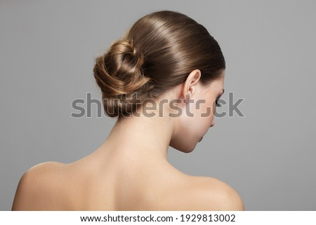 Woman with bun hairstyle on gray background. Bare back, shoulders and neck. Back view