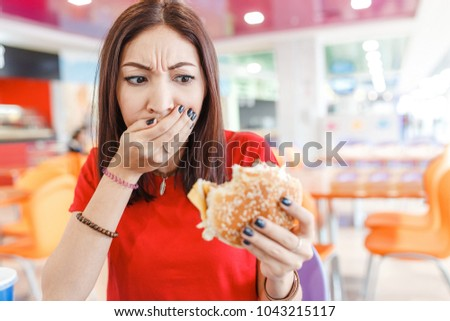 Woman with burger in hand, making bad and disgusting face, concept of the bad spoiled food and problems with digestion