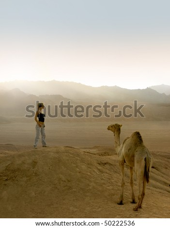 Woman with camel in desert