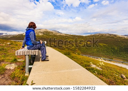 Woman with camera resting taking photo from Vedahaugane bench rest stop. National Tourist Route Aurlandsfjellet. Architecture Norway.