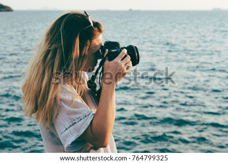 Photo of  Woman with camera shooting on the beach