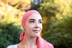 Woman with cancer wearing a pink scarf looking optimistic